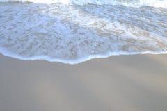Onde del mare sulla spiaggia pulita con la luce del sole immagine stock