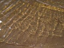 Onde della spuma sulla sabbia bianca fotografia stock