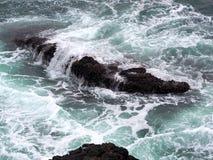 Onde di oceano che circolano sulle rocce irregolari della costa del Pacifico Immagine Stock