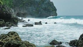 Onde di oceano che colpiscono la linea costiera di Tembeling all'isola di Nusa Penida, Bali Indonesia video d archivio