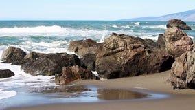 Onde di oceano che colpiscono le rocce su Sandy Beach stock footage