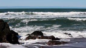 Onde di oceano che colpiscono le rocce su Sandy Beach Surfer In Background video d archivio