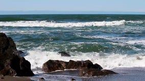 Onde di oceano che colpiscono le rocce su Sandy Beach Surfer In Background stock footage