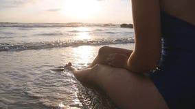 Onde di oceano che lavano sopra i piedi femminili abbronzati al tramonto Bella giovane donna che si rilassa sulla riva di mare du stock footage