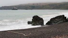 Onde di oceano contro roccia sulla spiaggia con il cielo nuvoloso video d archivio