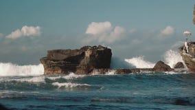 Onde di oceano dell'acqua blu che colpiscono e che spruzzano contro le rocce scure stock footage