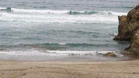 Onde di oceano sulla spiaggia di sabbia con le grandi rocce California archivi video