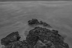 Onde di rottura che fanno le rocce fotografie stock