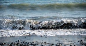 Onde di vento del mare che si schiantano sulla costa Immagini Stock