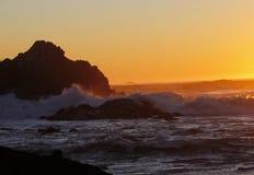 Onde dorate di spruzzatura e di tramonto a Tofino, BC immagine stock