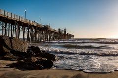 Onde e massi alla base del pilastro di pesca di riva dell'oceano fotografie stock libere da diritti