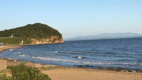 Onde enormi al litorale con la spiaggia sabbiosa e l'acqua di mare blu archivi video