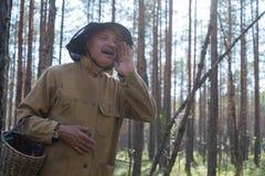 Onde está você conceito O homem europeu maduro vestido na roupa velha que guarda a cesta é perdido na floresta fotografia de stock royalty free