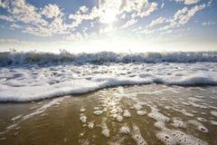 Onde lavant vers le haut du sable au coucher du soleil Photo stock
