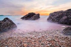 Onde molli dell'oceano nel tramonto con le pietre sulla priorità alta della spiaggia al parco nazionale Rayong di Khao Laem Ya MU Fotografia Stock Libera da Diritti