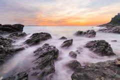 Onde molli dell'oceano nel tramonto con le pietre sulla priorità alta della spiaggia al parco nazionale Rayong di Khao Laem Ya MU Fotografie Stock Libere da Diritti