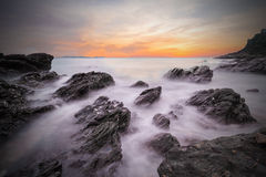 Onde molli dell'oceano nel tramonto con le pietre sulla spiaggia Fotografia Stock Libera da Diritti