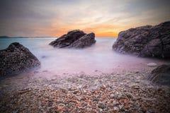 Onde molli dell'oceano nel tramonto con le pietre sulla spiaggia Immagini Stock Libere da Diritti