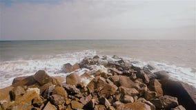 Onde nella rottura del mare sulle rocce sul litorale stock footage