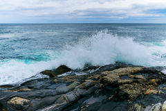 Onde potenti che si schiantano su una linea costiera rocciosa Immagine Stock