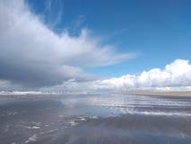 Onde a reunião das nuvens, da areia e da água fotografia de stock