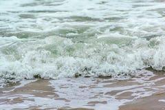 Onde spumose sulla spiaggia Immagine Stock