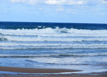Onde su un mare e su un cielo blu con le nuvole Fotografie Stock