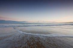 Onde su una spiaggia ad alba Fotografia Stock