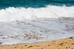 Onde sur la plage sablonneuse Blanc et bleu image libre de droits