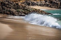 Onde sur une plage sablonneuse Photographie stock libre de droits