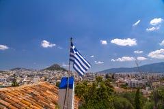 Ondeggiamento d'ondeggiamento della bandiera greca sopra la città di Atene fotografia stock libera da diritti