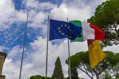Ondeggiamento delle bandiere dell'Unione Europea, dell'italiano e di Roma Immagine Stock