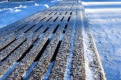 Onder een dunne laag sneeuwtribunes in de parkbank royalty-vrije stock foto