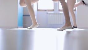 Onderaan mening van vrouwen die in modelschool veranderende benen springen stock footage