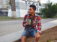 Onderbrekingstijd! Jonge Afrikaanse mens met de zitting van de koffiekop stock foto's