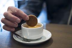 Onderdompelend een Nederlandse karamelwafel, genoemd Stroopwafel, in koffie royalty-vrije stock afbeelding