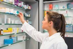 Ondergeschikte apotheker die geneeskunde van plank nemen stock foto