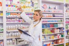 Ondergeschikte apotheker die geneeskunde van plank nemen royalty-vrije stock fotografie