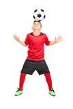 Ondergeschikte voetballer die met een bal hotsen stock foto's