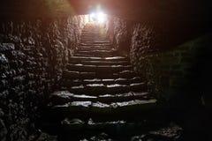 Ondergrondse passage onder oude middeleeuwse vesting Oude steentreden aan uitgang van tunnel stock foto's