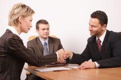 Onderhandeling over, man en vrouwenhanddruk stock afbeeldingen