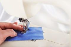 Onderhanden werk - naaimachine en hand van kleermaker met naald, draad en stof Punt van kleding royalty-vrije stock afbeelding