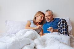 Onderhouden vrouwengevoel terwijl het letten van op komedie met echtgenoot royalty-vrije stock foto's