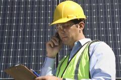 Onderhoudsarbeider die Celtelefoon met behulp van dichtbij Zonnepanelen Stock Foto's