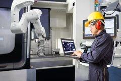 Onderhoudsingenieur die laptop de automatische robotachtige hand van de computercontrole met CNC machine in slimme fabriek, Indus royalty-vrije stock fotografie