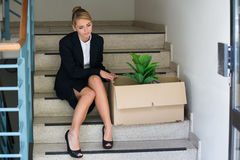 Onderneemster With Belongings Sitting op Stappen op Kantoor stock fotografie