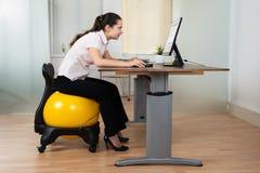 Onderneemster Bending While Sitting op Geschiktheidsbal stock afbeelding
