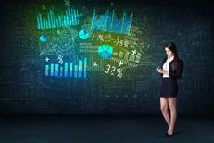 Onderneemster in bureau met in hand tablet en high-tech grafiek stock afbeeldingen