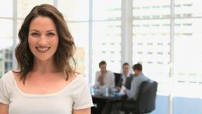 Onderneemster die aan de camera glimlachen terwijl haar team werkt stock videobeelden