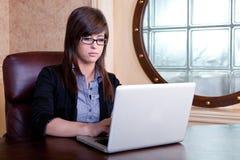 Onderneemster die aan haar laptop werkt Stock Foto's